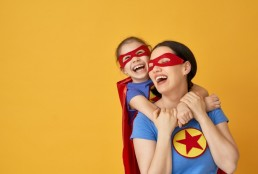 woman & child in matching superhero costumes, child on her back, both smiling laughing, yellow background.