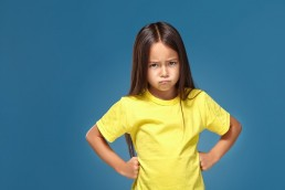 a pouting girl (child) wearing yellow with a blue background
